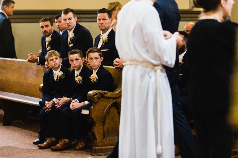 groomsmen boys and men with interesting expressions, while priest gives communion to congregation