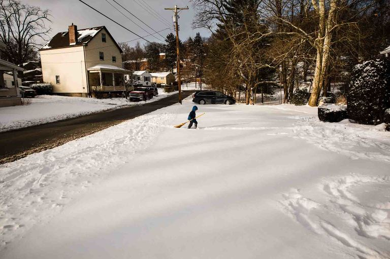 little boy in snowsuit walks through snowy front yard carrying a broom, body language dejected