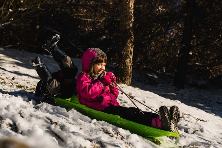 girl laughing and sledding while her friend falls off the sled with his feet in the air.