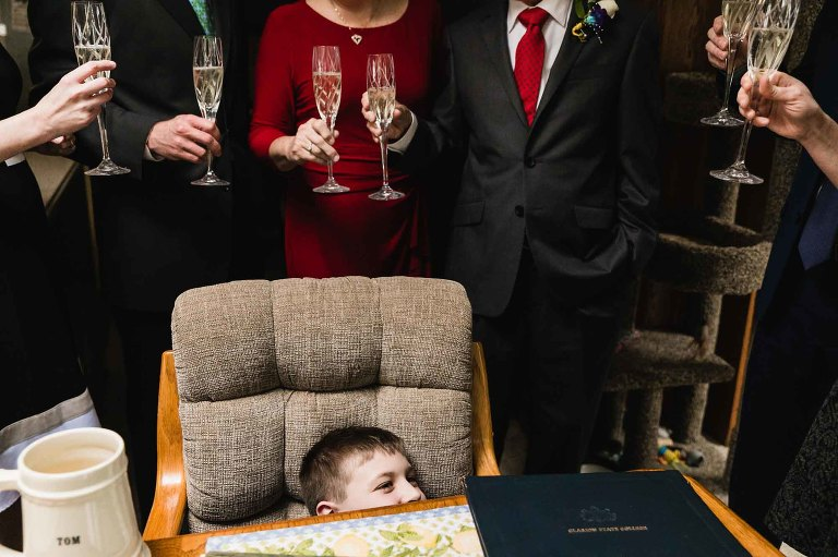 candid photo of boy hiding in a chair while the adults around him celebrate a special anniversary occasion.