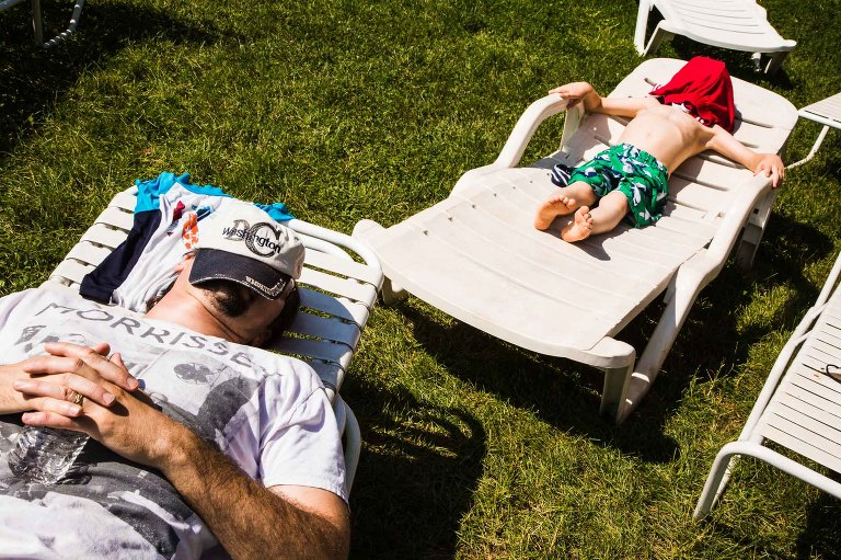 quiet moment of dad and his son laying in beach chairs, with similar body language