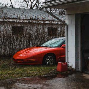 fancy red corvette car sits in the grass, alongside an adjacent open garage in an overgrown yard
