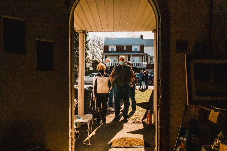 line of people outside estate sale front door waiting to enter