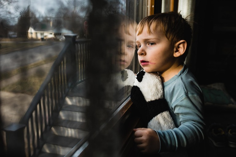 documentary photography picture of little boy sitting at the window