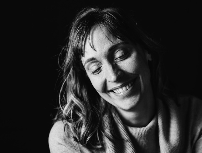 dramatic black and white portrait of a smiling woman. depicted is documentary photographer pamela anticole